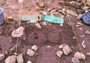 A closer vew of the socket in the stone that we believe marks the base of a post that supported the roof.