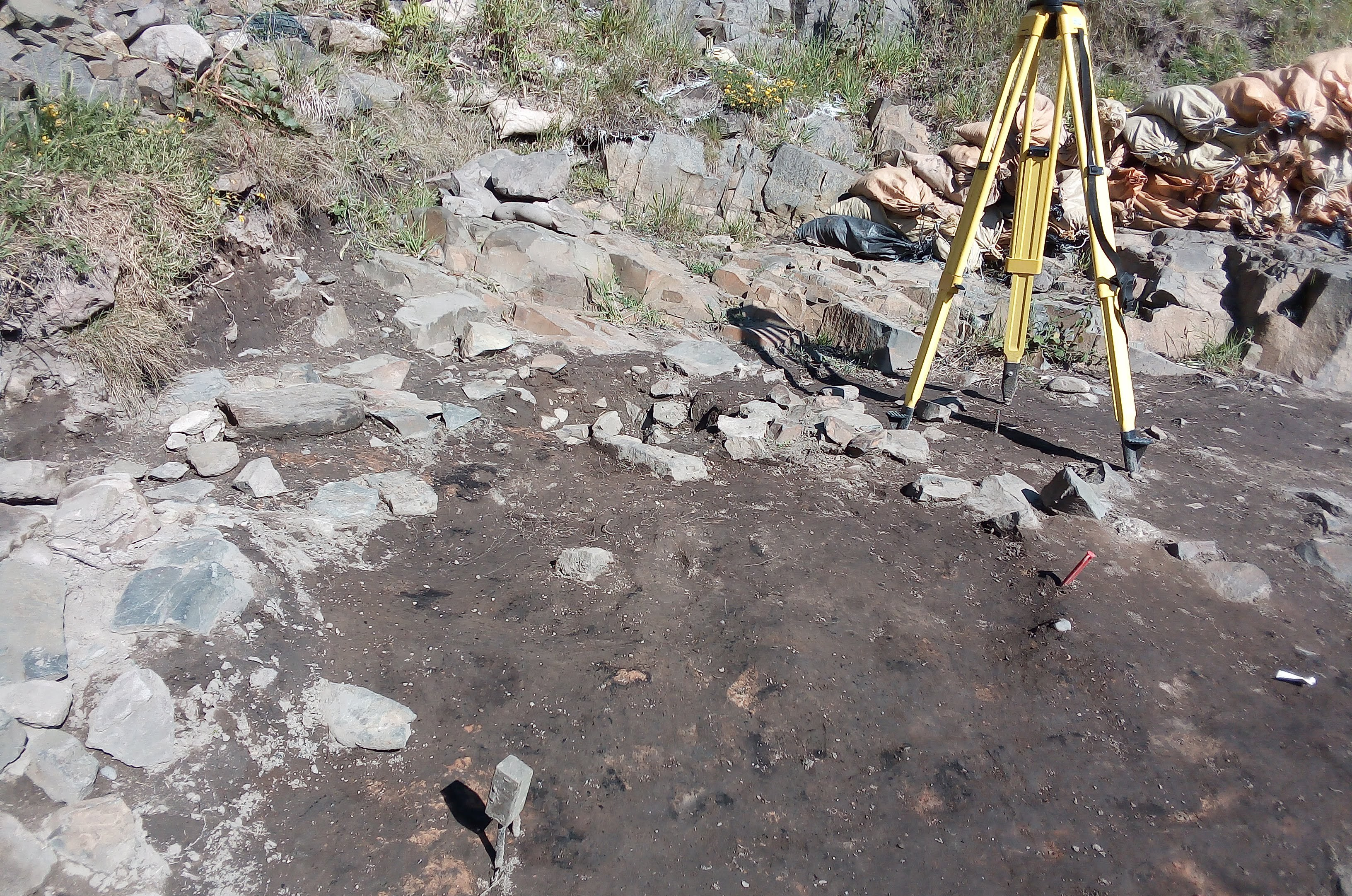 Yellow tripod in right background, triangle of grey-brown soil bordered on two sides by angular grey stones.