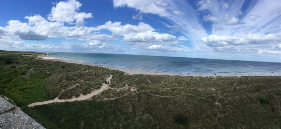 A panorama of partly cloudy blue skies, the North Sea, and grass-covered sand-dunes.