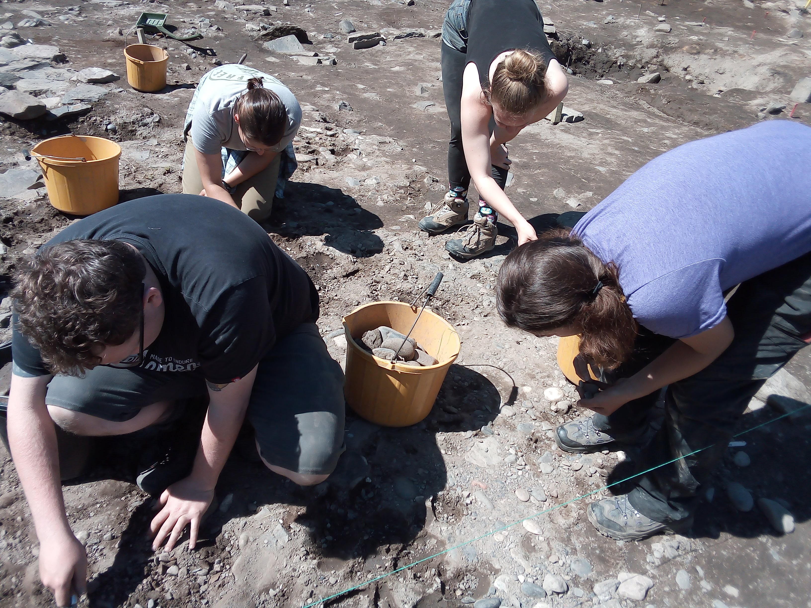 Four adults crouch to lift small grey and blue cobbles and place them in yellow buckets.