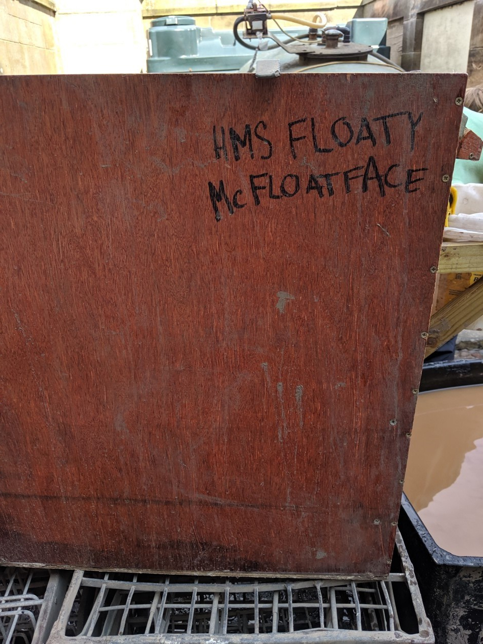 "A wooden tank labeled ""HMS Floaty McFloatface."""