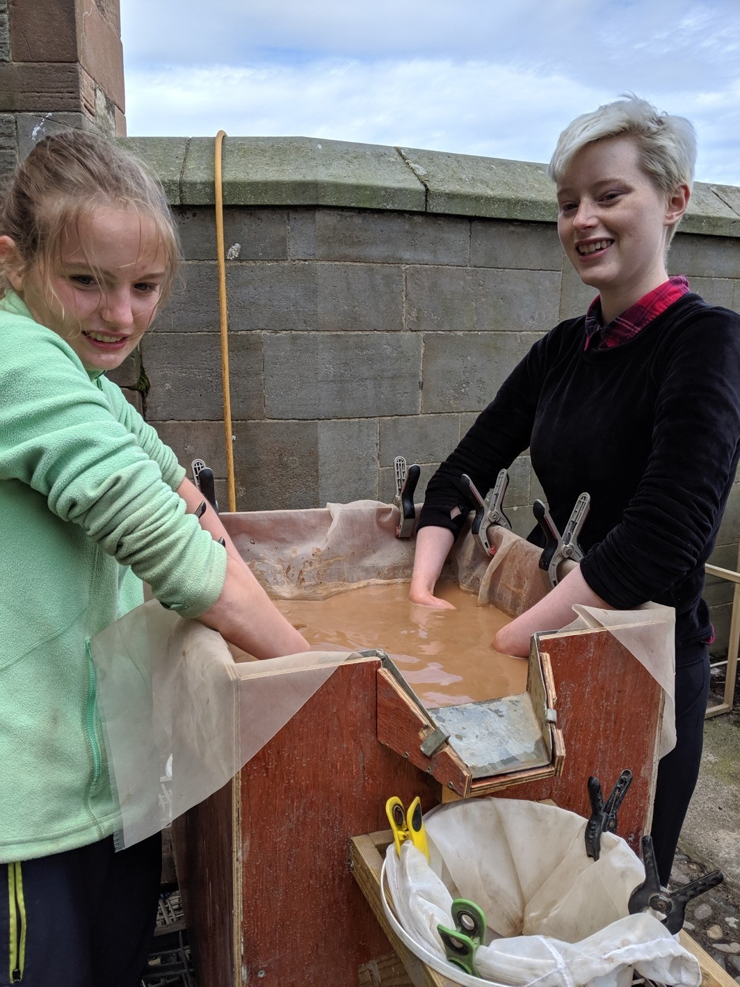 Two students with their hands in the flot tank.