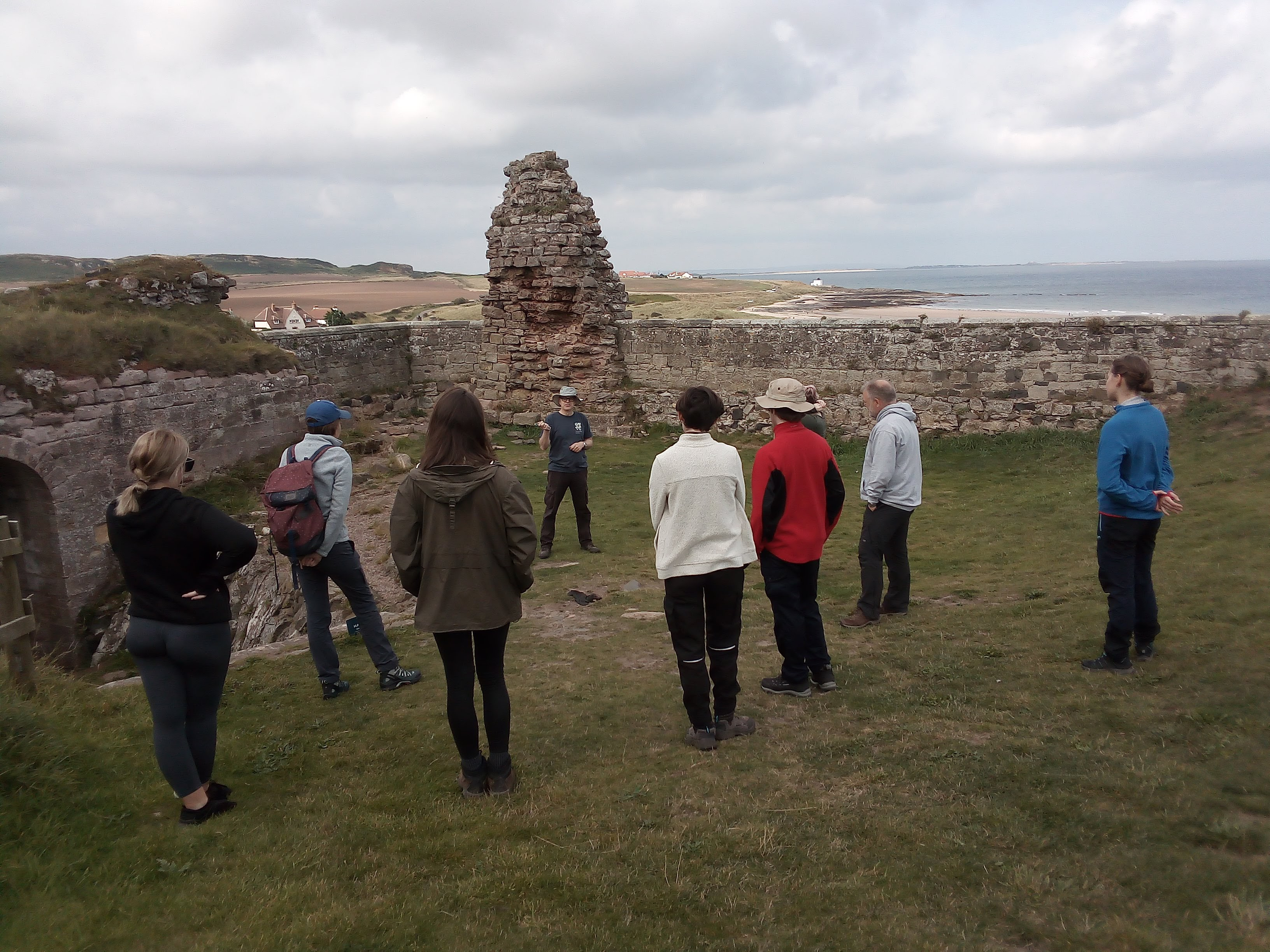 Students facing away from camera looking at co-director of the project in a bucket hat standing in front of an eroded bit of 12th-century masonry with the beach and North Sea in the background.