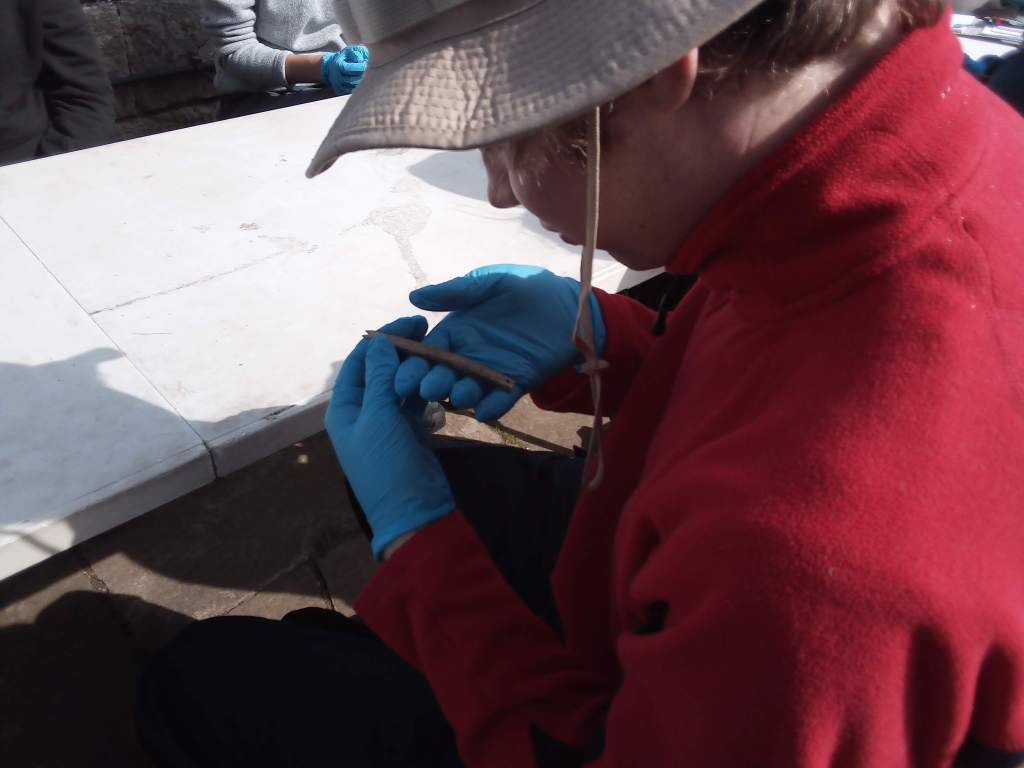 Student in red sweater holds small, rectangular and pencil-sized carved bone object.